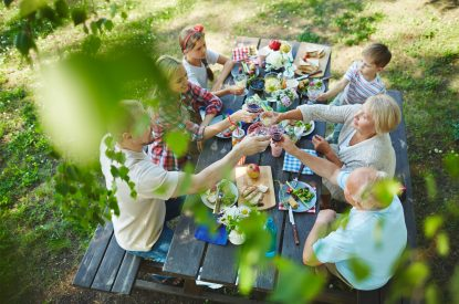 Young and senior couples cheering up with red wine by served table